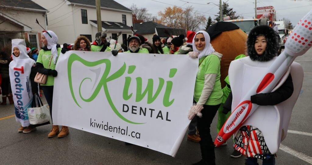 Kiwi Dental team holding a banner at the 70th annual Santa Claus parade in downtown Oakville